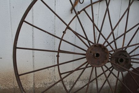 superannuated: Rusty wagon wheels leaning against a shed.
