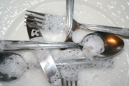 squeaky clean: Soapy  eating utensils up close on white dish.