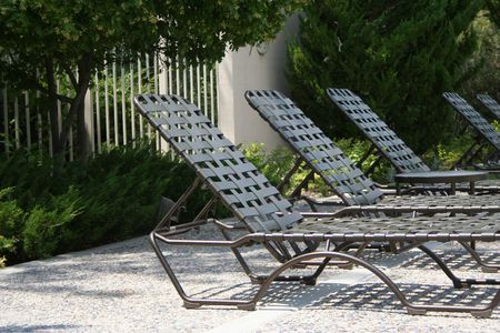 unoccupied: Sun tanning chairs lined up in a row.