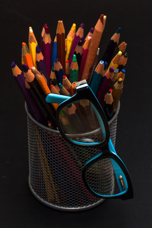 first year student: Colored pencils with glasses on blackboard Stock Photo