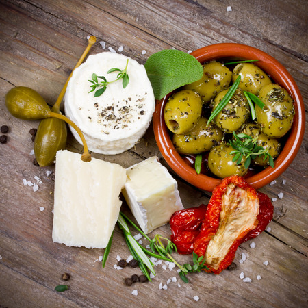 cheese platter: cheese and olives Stock Photo