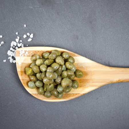 capers on wooden spoon