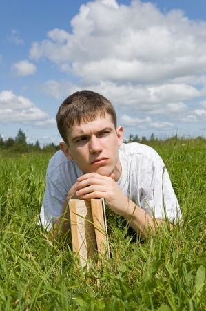 A young man reads a book, lying on a grass. photo