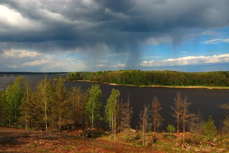 mountainside: Summer rain above the forest and water. Stock Photo