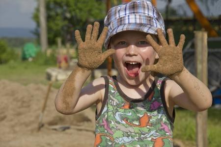 manos sucias: Ni�o jugando en el jard�n de arena con las manos