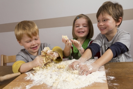masa: Ni�os haciendo la masa para hornear galletas de Navidad Foto de archivo