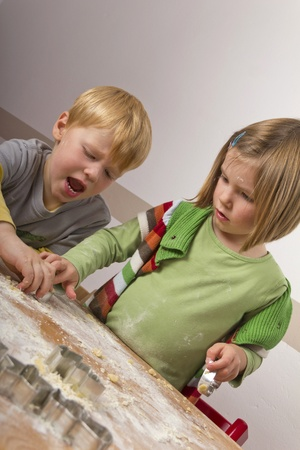 Two kids cutting cookies for christmas  Stock Photo - 11476849