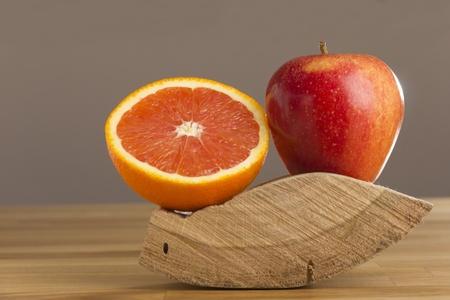 Orange and apple lying on wood Stock Photo