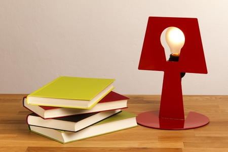 table lamp: Four books lying on a table, next to it a shiny lamp