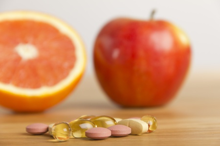 Dietary supplement in front of an apple and an orange