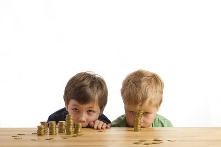Boys looking at towers of money Stock Photo - 12426404