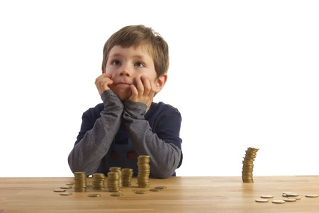 Boy sitting dreamily in front of towers, built out of money Stock Photo