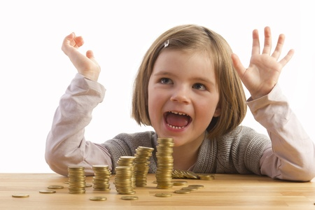 cash desk: A happy girl, sitting in front of money-towers
