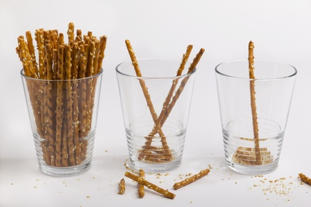 augmentation: Three glasses of saltsticks, from full to only one left Stock Photo