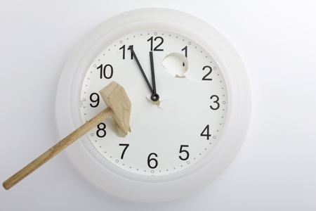 Broken clock with a hammer on it photo