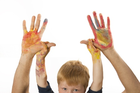 Boy holds the painted hands of his father photo
