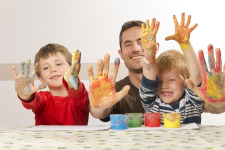 painting face: Father ist painting with his kids with finger paint