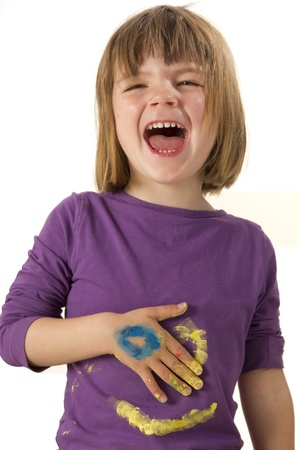 Girl painting with finger paint a face on her shirt photo