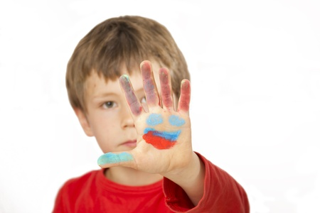 Boy is painting with finger paint a face on his hand Stock Photo - 13555095