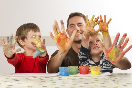 Father is painting with his kids with finger paint photo