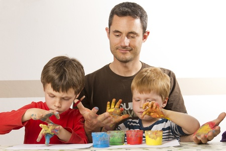 Father ist painting with his kids with finger paint Stock Photo - 13555097