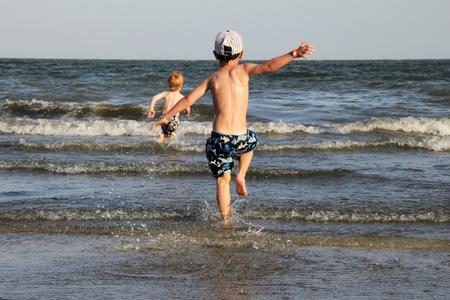 boy swim: Boy running into the sea Stock Photo