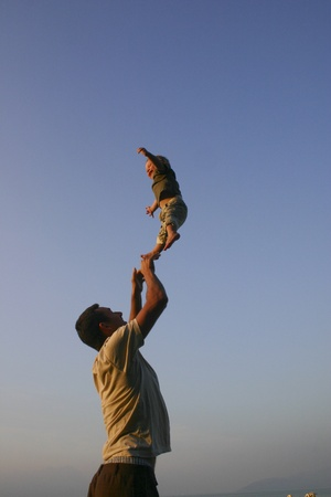 Father throwing his child into the air photo