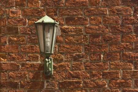 Red brick wall with a green lamp Standard-Bild