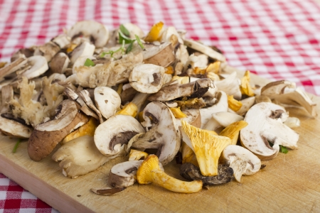 mixed fresh mushrooms, chopped on a wooden board