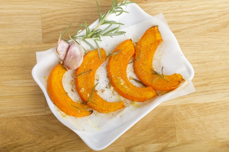 Baked pumpkin slices with rosemary and garlic Stock Photo