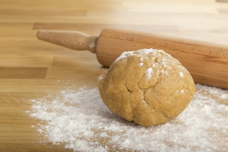 Dough lump on a wooden table with a rolling pin in the background