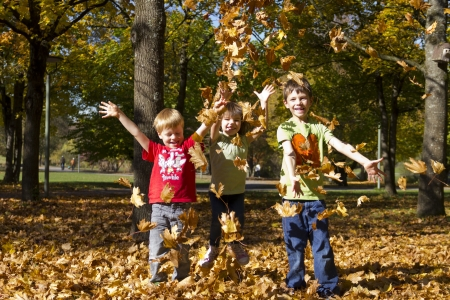Kids playing outside with colorful leaves in autumn