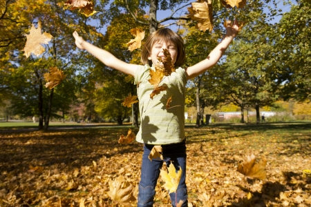 Girl playing outside with colorful leaves in autumn Stock Photo