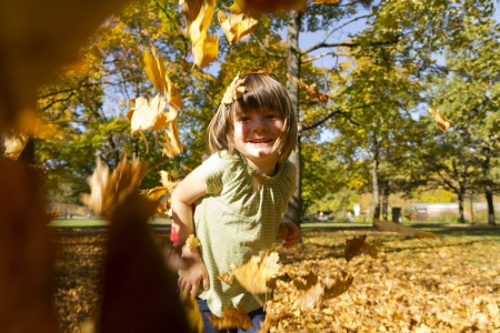 Girl playing outside with colorful leaves in autumn Standard-Bild