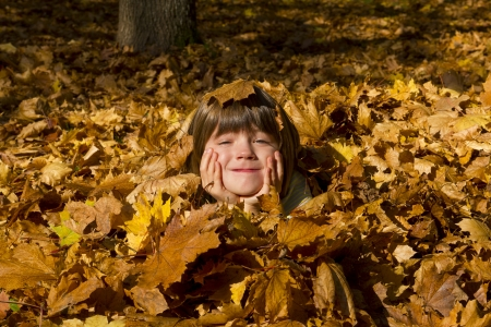 Girl laying in colorful leaves
