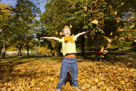 Boy playing outside with colorful leaves in autumn