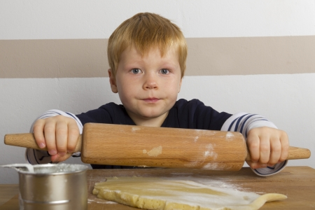 Boy rolls out doughwith a rolling pin photo