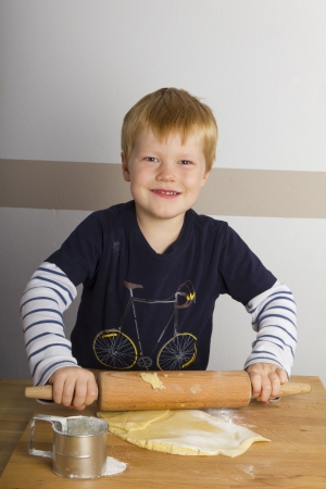 Boy rolls out dough with a rolling pin
