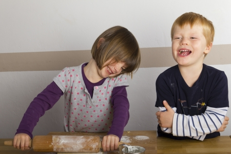 Kids rolling out dough with a rolling pin on the table photo