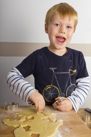 Boy is het uitsnijden van cookies Stockfoto