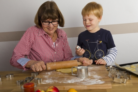 making fun: Grandmother and her grandchild cutting out cookies for christmas