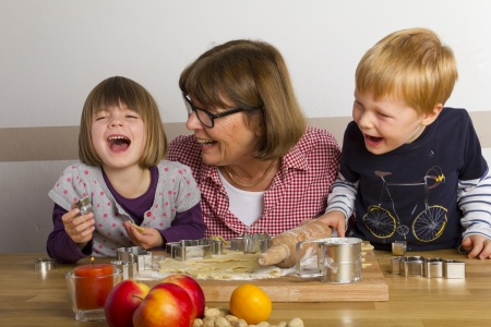 Grandma and her grandchildren cutting out cookies for christmas photo