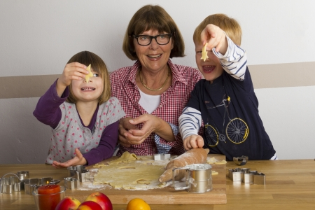 Grandma and her grandchildren cutting out cookies for christmas Stock Photo - 16192304