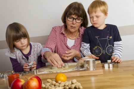 Grandma and her grandchildren cutting out cookies for christmas Stock Photo - 16192332