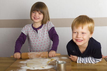 Children rolling out dough with a rolling pin