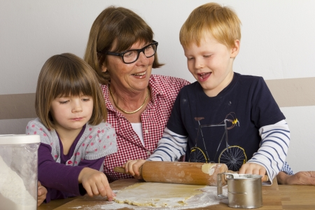 grandma and grandchildren rolling out dough photo