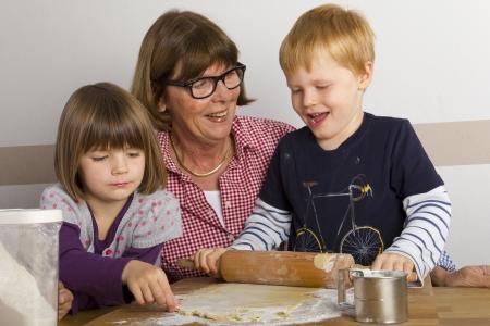 grandma and grandchildren rolling out dough