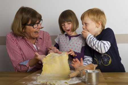 grandma and grandchildren rolling out dough