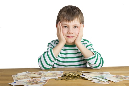 a lot of money: Young boy is sitting in front of a lot money