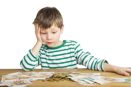 Young boy is looking amazed at a lot of money photo